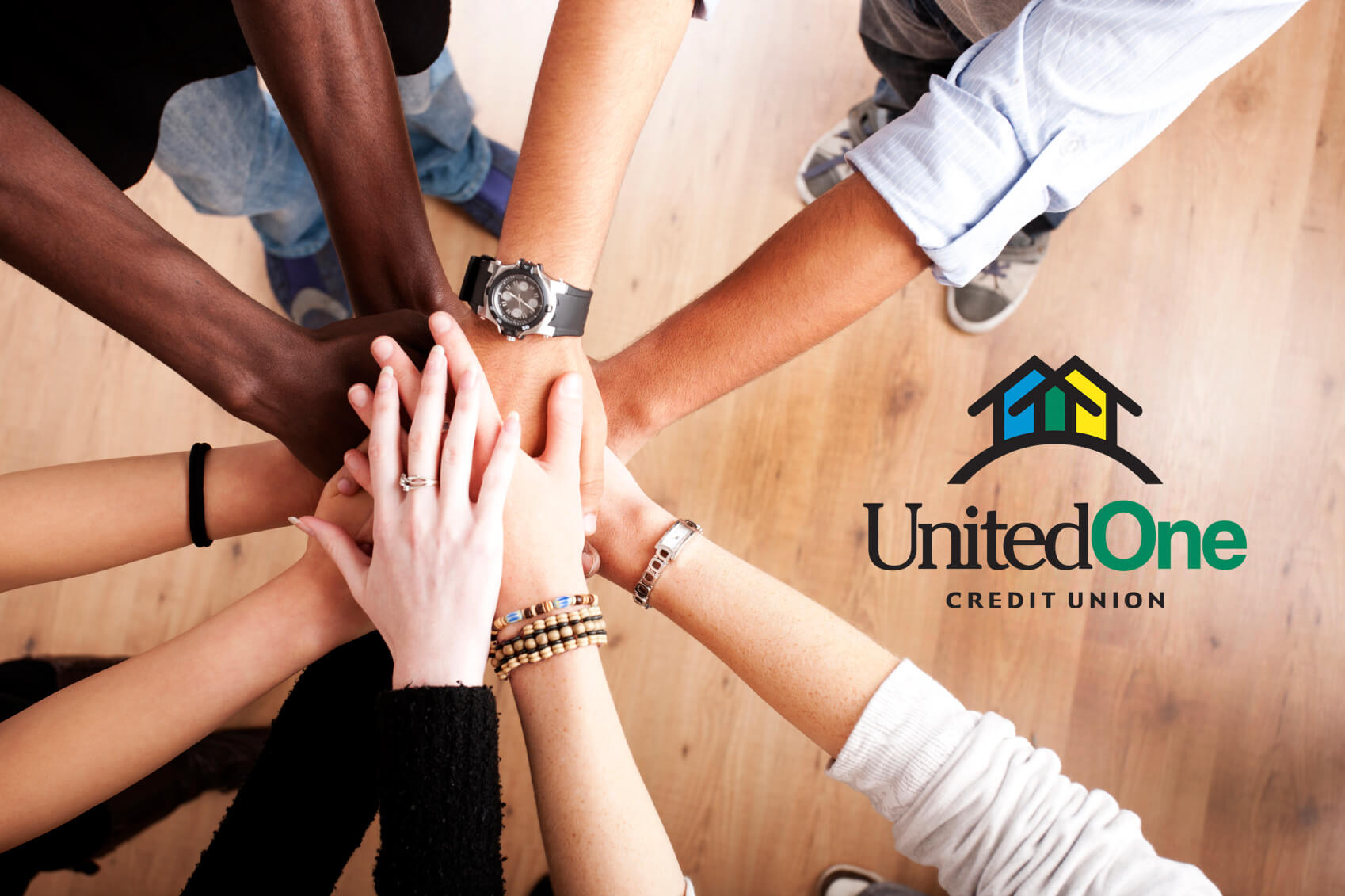 Group of people's hands as they huddle in a circle with UnitedOne Credit Union logo on the right.